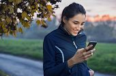 Young athlete looking at phone and smiling at park during sunset. Smiling young woman checking her s poster