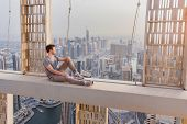 Roofer sits on concrete cross beam of Cayan Tower (Infinity Tower) in Dubai, UAE poster