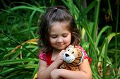 foto of stuffed animals  - Four year old girl cuddling with her stuffed animal tiger - JPG