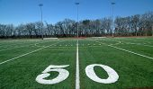 foto of football field  - 50 Yard Line Football Field with lights in the background - JPG