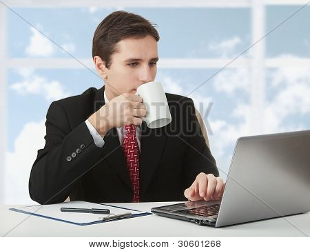 Hombre de negocios exitoso joven trabajando detrás de la Notebook, sentado en un escritorio con una taza de café en
