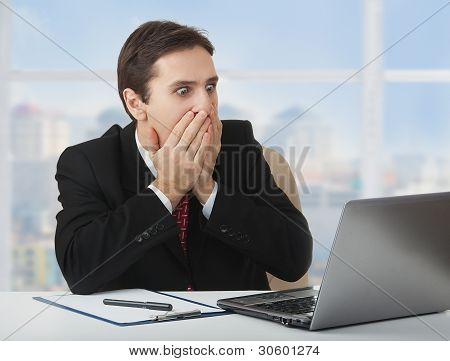 Surprised  Frightened Businessman   Looking At A Laptop, His Hands Covering His Mouth With Fear And