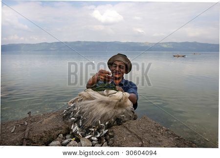 SUMATERA - FEBRUARY 10: A fisherman displays his catch from Lake Singkarak, a tectonic lake in Sumatera, Indonesia on Feb 10, 2012. It is the biggest lake in Sumatera measuring 20km long and 8km wide.