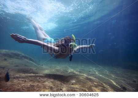 Young woman freediving in a clear tropical sea with sandy bottom