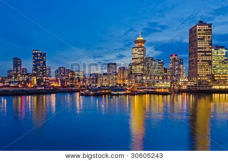 City at night, panoramic scene of downtown reflected in water, Vancouver, Canada.