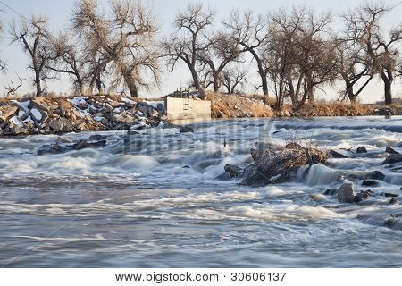 a small dam diverting water to farmland irrigation, South Platte River in eastern Colorado near Greeley, winter scenery
