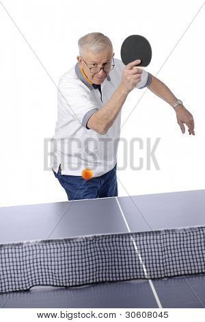 A senior man ready to whack the ping pong ball back across the net.  Motion blur on ball.  On a white background.