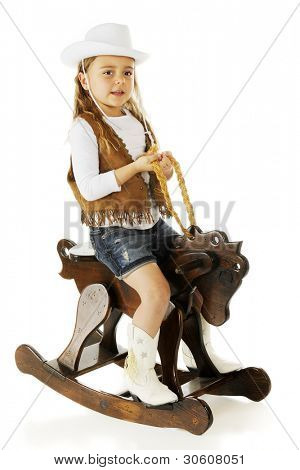 "An adorable kindgergarten ""cowgirl"" actively riding a wooden rocking horse.  On a white background."