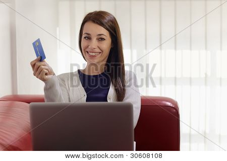 Woman With Laptop And Credit Card Shopping On Internet