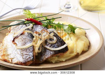 Filetes de trucha a la plancha dos con puré de papas y hierbas en un plato marrón