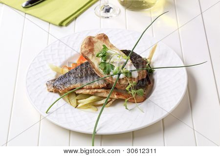 Two grilled trout fillets with vegetables on a white plate