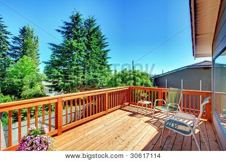 Large New Wood Deck Home Exterior With Chairs.