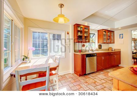Charming Cherry Wood Kitchen With Tile Floor.