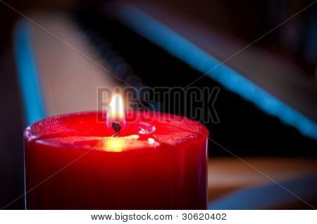 Red candle and blurred synthesizer in the background