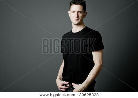 Young strong man in black t-shirt on gray background.