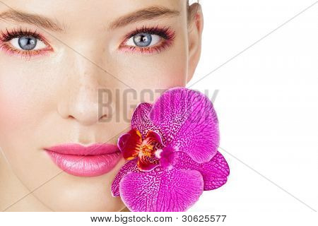 Woman with pink makeup and purple orchid. Space for text.