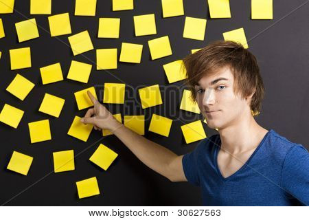 Young student pointing to a board full of yellow notes and looking in to the camera