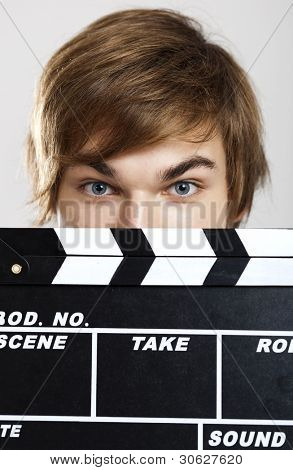 Portrait of a young man peeking behind a clapboard, over a gray background