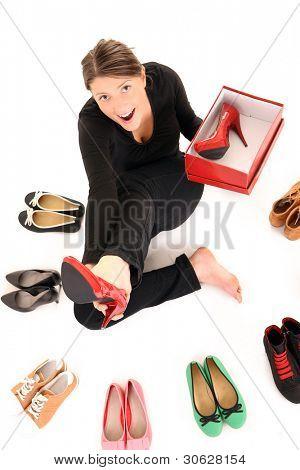 Ein Bild von einer jungen Frau, die versucht, auf neues Paar Heels over white background