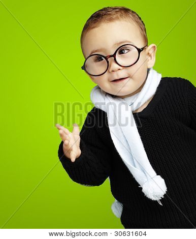 portrait of adorable kid gesturing doubt against a green background