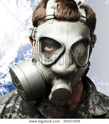 portrait of young soldier wearing gas mask against a cloudy sky background