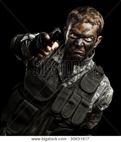 portrait of furious soldier with urban camouflage pointing with gun over black background