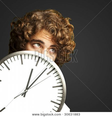 scared young man hidden behind a clock against a black background