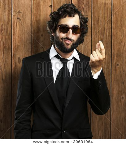 portrait of business man doing money sign against a wooden wall
