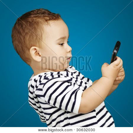 portrait of funny kid touching mobile over blue background