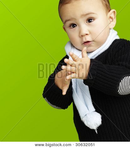 portrait of adorable kid clapping against a green background
