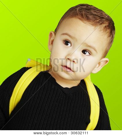 portrait of adorable kid carrying yellow backpack over green background