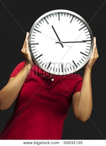woman holding clock in front of head against a black background