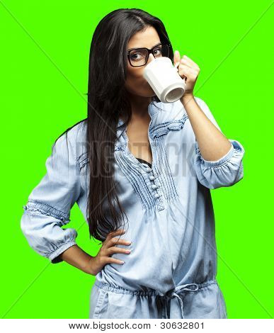 portrait of young woman drinking coffee against a removable chroma key background
