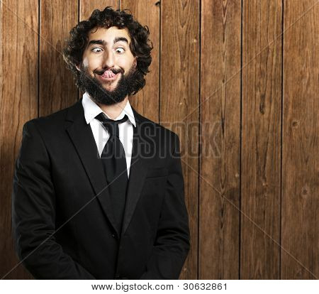 portrait of young business man showing tongue against a wooden wall