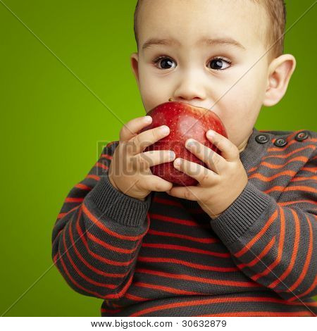 portrait of a handsome kid sucking a red apple over green backgr