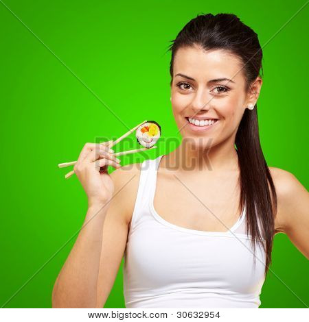 young woman holding a piece of sushi with chopsticks against a green background