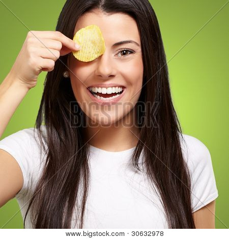 portrait of young woman holding a potato chip in front of her eye over green