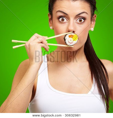 young woman covering her mouth with a sushi piece against a green background
