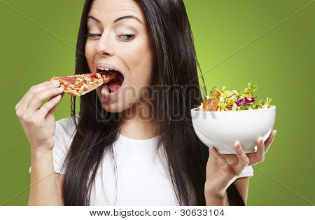 woman choosing a slice of pizza instead of a salad against a green background