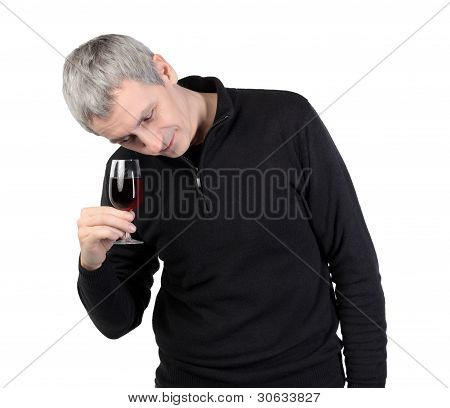 Man looks at a glass of red port wine