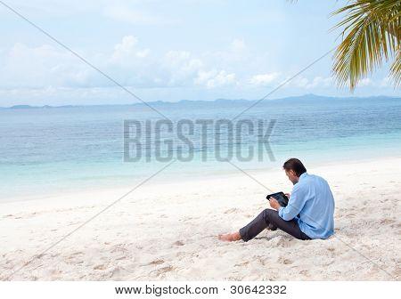 Hombre de negocios sentado y trabajando en la playa con tablet PC