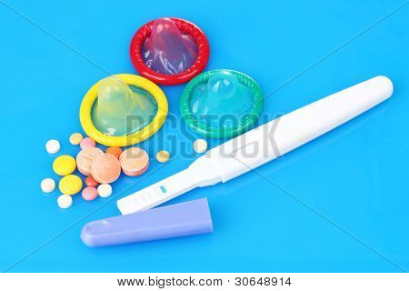 birth condoms, pregnancy test and control pills on blue background