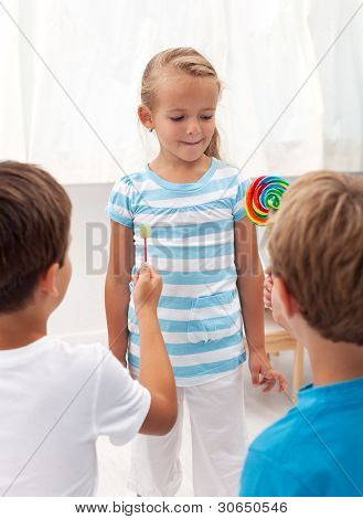 Boys courting a little girl with lollipops