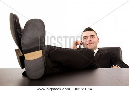 Young business man relaxing at office desk and talking on mobile phone, isolated on white