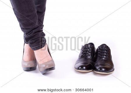 Men's shoes near the women's feet
