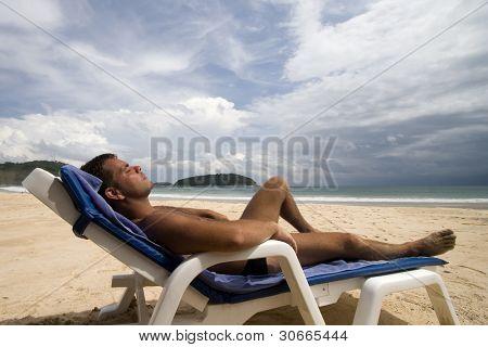 tanned man laid on a chair at a white sand beach, Phuket Island, Thailand