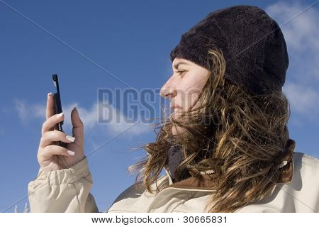 Young woman holding a mobile phone, outdoor.