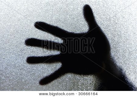 Diffuse image of a hand against glass