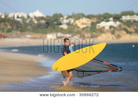 summer sports: windsurfer with yellow board on the beach, Algarve, south of Portugal