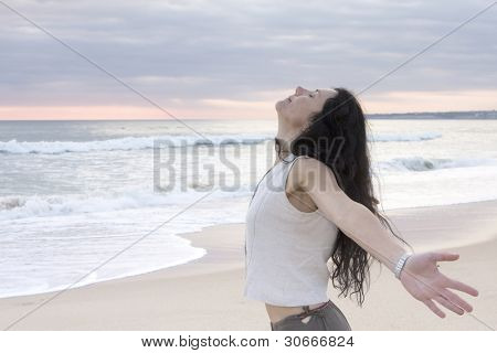 Happy female at beach throwing her arms back behind her